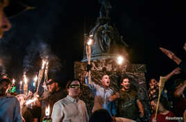 FILE - White nationalists participate in a torch-lit march on the grounds of the University of Virginia ahead of the Unite the Right Rally in Charlottesville, Virginia, on Aug. 11, 2017.