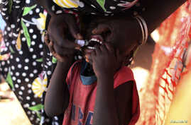 A displaced South Sudanese child receives an oral cholera vaccine in a camp for internally displaced people in the United Nations Mission in South Sudan (UNMISS) compound in Tomping, Juba February 28, 2014