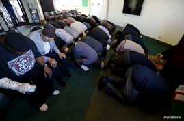 FILE - People pray at the Ahmadiyya Muslim Community Baitus-Salaam Mosque during an open mosque event at which members of the public are invited to see how Ahmadiyya Muslims pray, in Hawthorne, California.