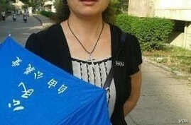 Liu Ping holding an umbrella with slogans of the New Citizens' Movement.