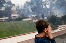 A woman cries as she covers her face near her destroyed home after a wildfire swept through Ventura, Calif., Dec. 5, 2017.