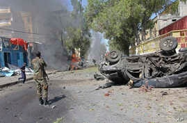 A Somali soldier stands near the burning wreckage of a car, after an explosion, in Mogadishu Somalia, Oct. 1, 2016.