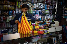 A seller organizes esteladas or independence flags to sell in a shop in Barcelona, Spain, Oct. 11, 2017.
