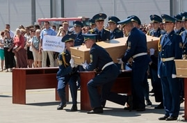 Ukrainian honor guards lift up a coffin, holding the body of one of the Malaysian Airlines plane passengers, to load it onto a Dutch cargo plane in Kharkiv airport, Ukraine, Wednesday, July 23, 2014. The Dutch government has declared Wednesday a day