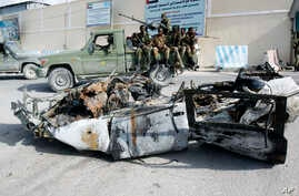 Somali soldiers sit on a pickup truck near the wreckage of a car bomb that was detonated at the main gate of the presidential palace in Mogadishu, July, 9, 2014.