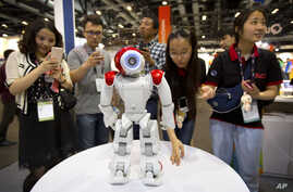 FILE - Visitors watch as a robot from Aldebaran Robotics dances at the Global Mobile Internet Conference in Beijing, April 29, 2015.