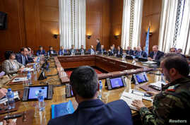 Syria's main opposition High Negotiations Committee leader Naser al-Hariri and UN Special Envoy of the Secretary-General for Syria Staffan de Mistura attend a round of negotiation, during the Intra Syria talks, at the European headquarters of the Uni
