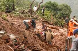 Rescue workers carry the body of a victim at the site of a landslide in Malin village, in the western Indian state of Maharashtra, July 30, 2014.