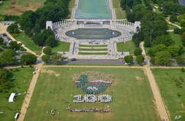 People on the National Mall in Washington, looking toward the World War II Memorial, Aug. 25, 2016, recreate a giant, living version of the National Park Service emblem, using  brown, green and white umbrellas.