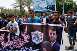 FILE - Hundreds of supporters of exiled former Gaza strongman Mohammed Dahlan carry a banner with his picture during a protest against metal detectors Israel erected at the Al-Aqsa Mosque compound in Jerusalem, in Gaza City, July 20, 2017.