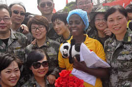 Ebola patient Beatrice Yardolo, center, surrounded by Chinese military health workers, as she leaves the Chinese Ebola treatment center were she was treated for the Ebola virus infection  outskirts of Monrovia, Liberia,  March 5, 2015.