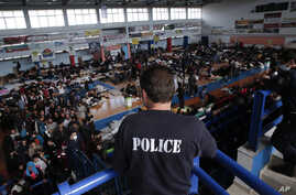 A policeman observes the scene as immigrants who arrived aboard a cargo ship from Turkey queue for meals in a basketball arena where they have been given temporary shelter in the town of Ierapetra, Crete, Nov. 28, 2014.