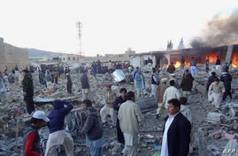 People gather after a bomb targeting Shiite Muslims exploded in busy market in Hazara town, an area dominated by Shiites on the outskirts of Quetta, on Feb. 16, 2013.