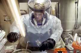 FILE - Microbiologist Ruth Bryan works with BG nerve agent simulant in Class III Glove Box in the Life Sciences Test Facility at Dugway Proving Ground, Utah, May 11, 2003.