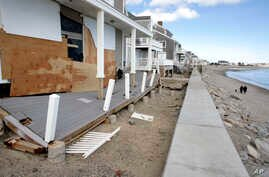People walk along a beach near damaged beachfront homes, March 11, 2018, in Marshfield, Mass. The Northeast is bracing for its third nor'easter in fewer than two weeks.