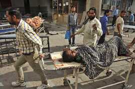 An Indian woman is brought to a government medical college hospital after she was injured in firing by Pakistani troops across the India-Pakistan border at Jora farm in Ranbir Singh Pura, in Jammu, India, Oct. 8, 2014.