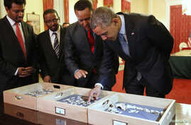 Dr. Zeresenay Alemseged Lemseged (2ndR), of the California Academy of Sciences, directs U.S. President Barack Obama (R) to touch a fossilized vertebra of Lucy, an early human, before a State Dinner in Obama's honor at the National Palace in Addis Aba