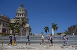 FILE - People walk past the Capitol, where renovation work was underway, in Havana, Cuba, March 10, 2016.