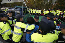 South Korean policemen stop a Paju resident from rushing to an anti-North Korean civic group's vehicle near the demilitarized zone separating the two Koreas in Paju, Oct. 25, 2014.