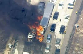 In this frame from video provided by NBC4, smoke rises from vehicles as a fast-moving wildfire swept across a freeway near Hesperia, Calif., July 17, 2015.