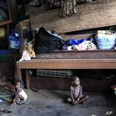 Ivorian toddlers Prencia Gosse, left, and Laure Djiejian, who along with their families fled ethnic and political clashes, play alongside piled belongings in a classroom at the Catholic Mission in Duekoue, in western Ivory Coast (File Photo - May 30,