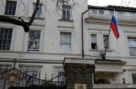 A man works to untangle the national flag flown from the Russian Embassy, after it became entangled on its staff at the embassy in London, March 14, 2018. Britain announced Wednesday it will expel 23 Russian diplomats, the biggest such expulsion sinc