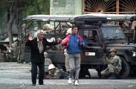 FILE - Local residents walk with their hands raised as Uzbek soldiers take positions to disperse protesters in Andijan, Uzbekistan, May 13, 2005. Several hundered people are thought to have been killed during the crackdown.