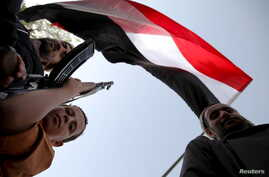 A boy holding a weapon stands under a Yemeni national flag, as followers of the Houthi group demonstrate against an arms embargo imposed by the U.N. Security Council on the group in Sanaa, April 16, 2015.