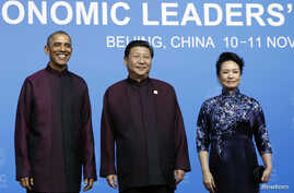 U.S. President Barack Obama, left, poses for photographs with China's President Xi Jinping, center, and Xi's wife, Peng Liyuan, during the APEC Welcome Banquet at Beijing National Aquatics Center in Beijing, Nov. 10, 2014.