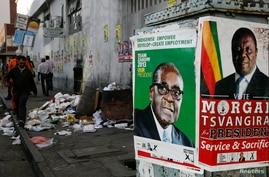 Election campaign posters are pictured near Zimbabweans walking on a street blocked by uncollected garbage in Harare July 17, 2013.