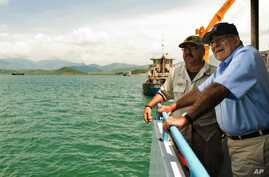 U.S. Secretary of Defense Leon Panetta, right, talks with Chief Mate Fred Cullen as he takes a boat out to a U.S. navy cargo ship USNS Richard E. Byrd in Cam Ranh Bay, Vietnam, June 3, 2012.