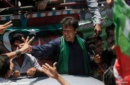 Imran Khan, Pakistani cricketer-turned-politician and chairman of political party Pakistan Tehreek-e-Insaf (PTI), cheers his supporters after his visit to the mausoleum of Mohammad Ali Jinnah, founder and first governor-general of Pakistan, during an...