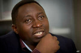 FILE - Frank Habineza, the leader of Rwanda's only opposition political party the Democratic Green Party of Rwanda, speaks to a reporter at his offices in Kigali, Rwanda.