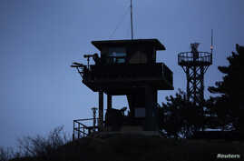 A South Korean soldier uses binoculars to look out to sea from a watchtower on Yeonpyeong island, which lies just inside the South Korean side of the Northern Limit Line, in the Yellow Sea, April 8, 2014.