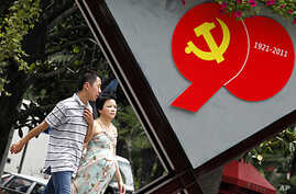 A couple walks past an advertisement to celebrate the upcoming 90th anniversary of the founding of the Communist Party of China on July 1, in Shanghai, China, June 22, 2011.