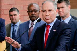 """FILE - Environmental Protection Agency Administrator Scott Pruitt speaks at a news conference with Pasquale """"Nino"""" Perrotta (2nd-L) in East Chicago, Ind., April 19, 2017."""