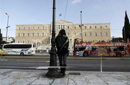 A woman stands opposite the Parliament in central Athens, Tuesday, Nov. 27, 2012. Greece has avoided imminent bankruptcy after its international creditors finally agreed early Tuesday to give it the money it urgently needs. But the cash-strapped coun