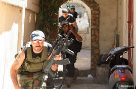 Sunni Muslim gunmen run to take up position in the neighbourhood of Bab al-Tebbaneh in Tripoli, northern Lebanon, during sectarian clashes between Sunni Muslims and Alawites August 24, 2012.