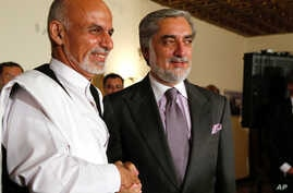 Afghan presidential candidates Ashraf Ghani and Abdullah Abdullah shake hands during a joint press conference in Kabul on July 12, 2014.  US Secretary of State John Kerry on July 12 held a second day of talks with Afghanistan's feuding presidential h