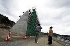 FILE - Local residents look at the 12.5-meter (41-foot)-high concrete barrier under construction in the northern fishing port of Osabe, in Rikuzentakata, Iwate Prefecture, northeastern Japan, March 12, 2015.