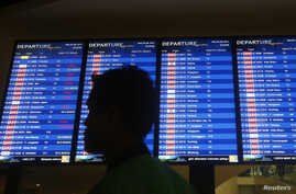 A man walks in front of a flight board at Kuala Lumpur International Airport 2 (KLIA2) in Sepang, Apr. 30, 2014.