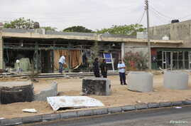 A man cleans his shop after a suicide car bomber blew himself up at a checkpoint in Dafniya outside Mistrata, Libya, May 31, 2015.