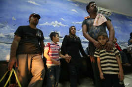 Asylum seekers rescued from heavy seas off Java, wait inside a temporary detention room upon arrival at a local marine police station in Surabaya, East Java, Indonesia, July 29, 2012.