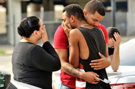 Friends and family members embrace outside the Orlando Police Headquarters during the investigation of a shooting at the Pulse night club in Orlando, Florida, June 12, 2016.