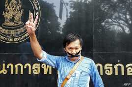 Thai journalist Pravit Rojanaphruk flashes a V-sign as he stands with his mouth taped outside a military base in Bangkok where he had been summoned by the junta, May 25, 2014.