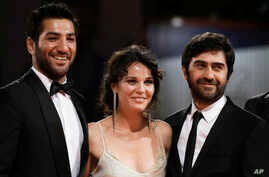 From left, actors Berkay Ates, Tulin Ozen, and director Emin Alper pose during the red carpet for the film Frenzy (Abluka) at the 72nd edition of the Venice Film Festival in Venice, Italy, Sept. 8, 2015.