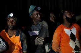 Miners look on after they retrieved the bodies of two other miners from Johannesburg's oldest gold mine in Langlaagte, South Africa, September 13, 2016.