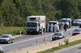 Police stand near a truck stopped on the side of the highway near Parndorf south of Vienna, Austria, Aug 27, 2015. Officials say up to 50 migrants were found dead in the truck. They reportedly suffocated.