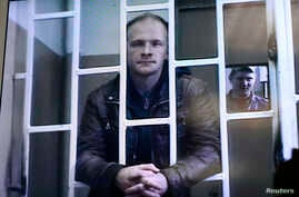 Photographer Denis Sinyakov, one of 30 people detained after a Greenpeace protest at Prirazlomnaya platform, is seen on a screen inside a court building during a court session in Murmansk, Russia, Oct. 8, 2013.