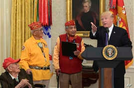 President Donald Trump, right, speaks during a meeting with Navajo Code Talkers including Fleming Begaye Sr., seated left, Thomas Begay, second from left, and Peter MacDonald, second from right, in the Oval Office of the White House, Nov. 27, 2017.